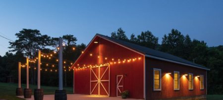 Red barn venue lit with edison lights at dusk