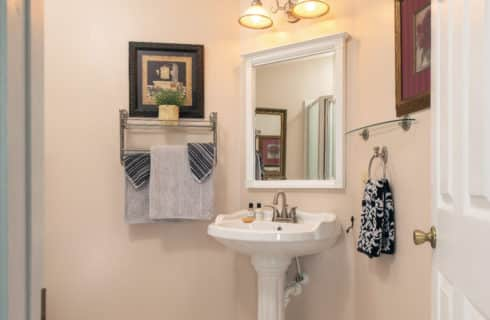 Airy bathroom with white pedestal sink and large mirror