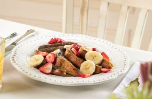 French toast with bananas and strawberries with whipped cream and link sausage on a white plate served with orange juice.