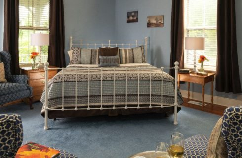 Bedroom painted light blue with white rod-iron headboard and footboard