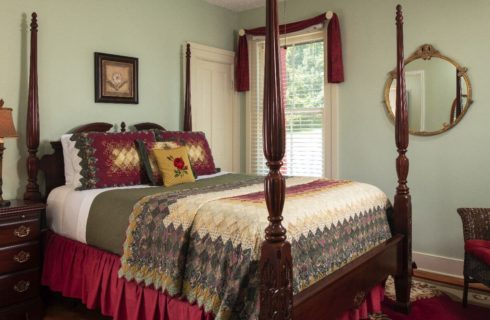 Elegant guest room with a large dark wood four-poster bed and burgundy accents