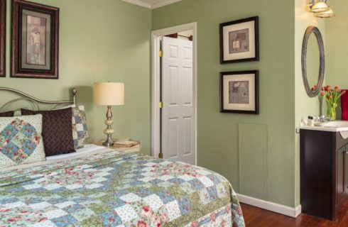 Cheery guest room with light green walls and large bed covered in a coordinating quilt.