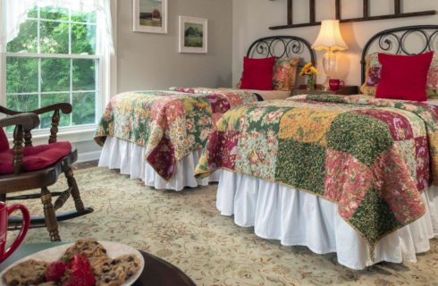 Airy farmhouse room with large windows shown made up with twin beds.