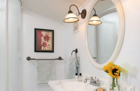 Clean white private guest bath with pedestal sink and large mirror.