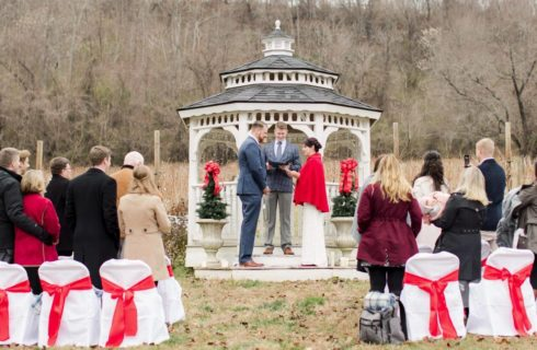Bride and Groom standing at gazeboo decororated in red for wedding,