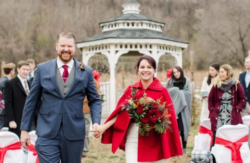 Happy grooom and bride in a white gown with a red cloak walking down aisle.