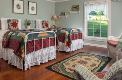 Large room shown with 2 white iron twin beds made up with colorful quilts.