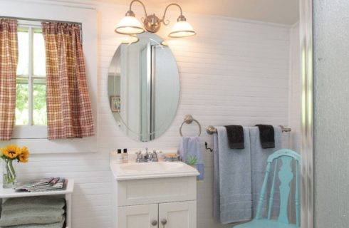 Large and airy white bathroom with a vanity sink.