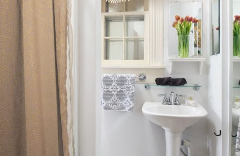 Clean and elegant bathroom with a pedestal sink and window.