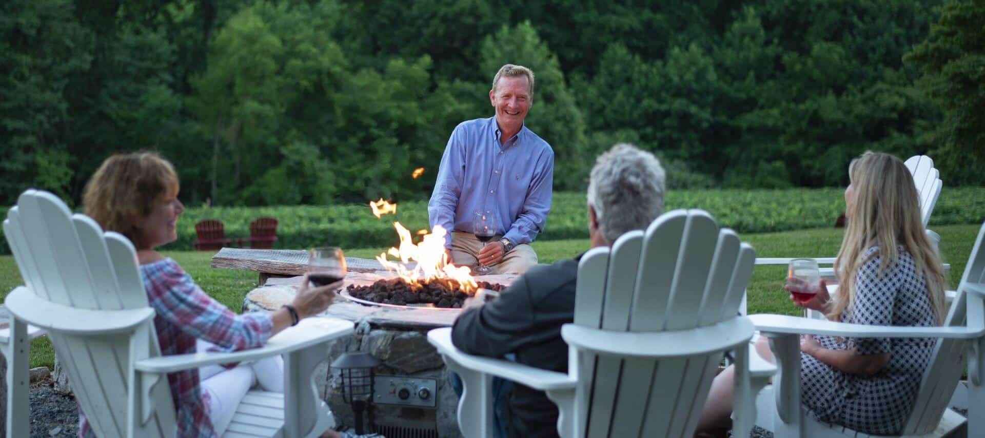 Smiling man in a blue shirt sitting by a firepit with people in white adirondack chairs