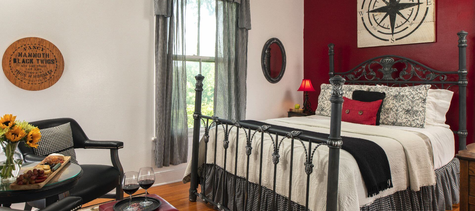 Large black bedstead in a room decorated in whtie with black and red touches.