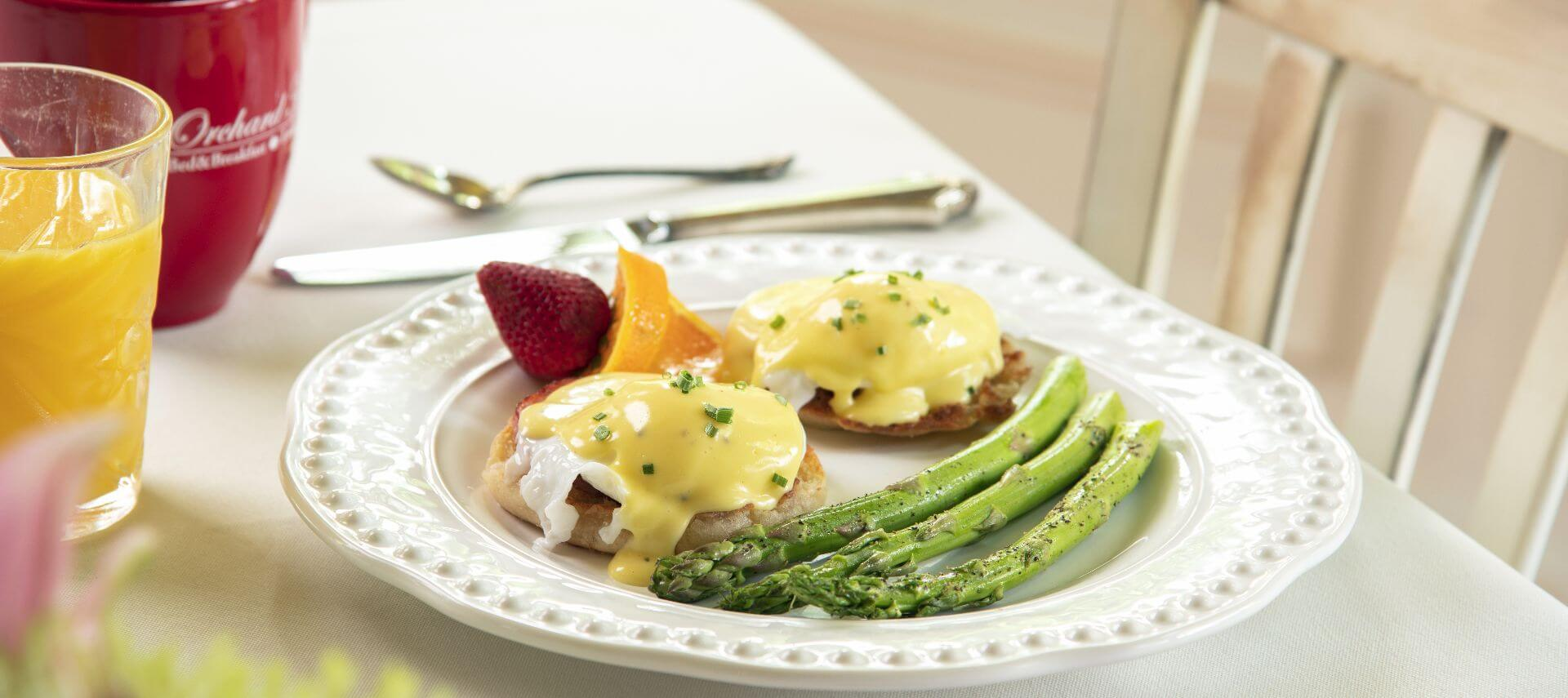 Eggs benedict served with asparagus on a white plate with fruit.