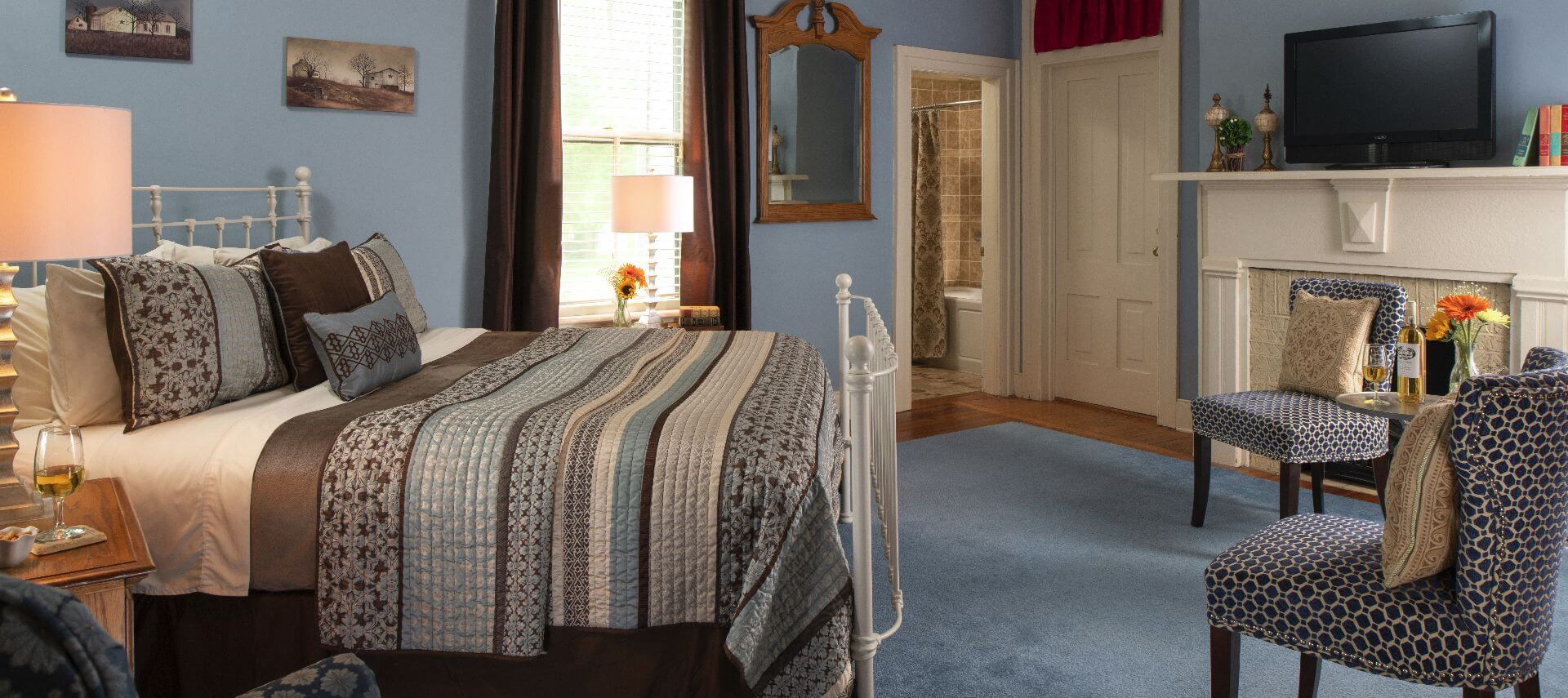 Comfortable room with blue walls and carpet and a white bedstead.