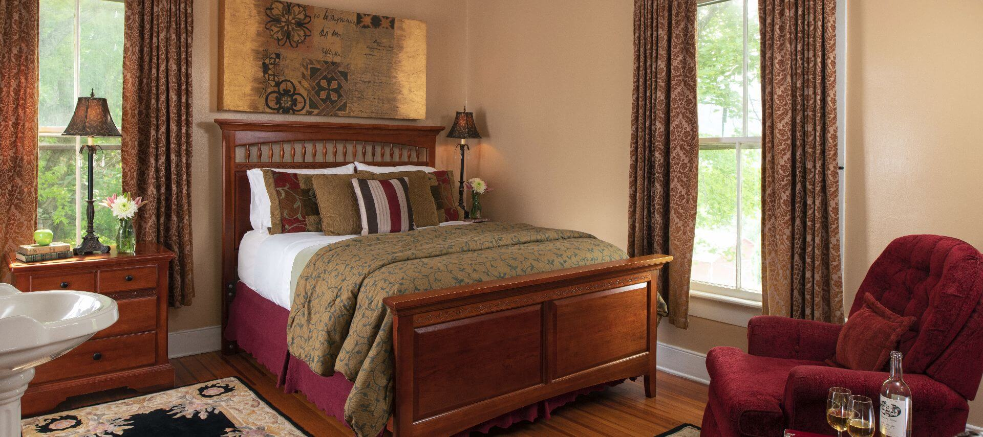 Elegant wooden sleigh bed covered insumptuous bedding in large airy room.