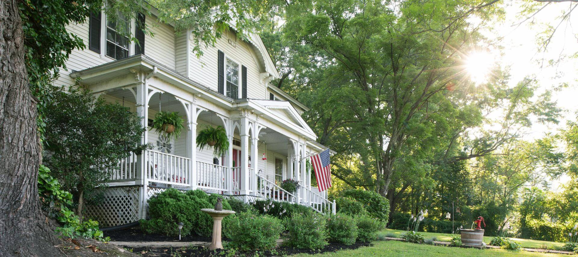 White manor hosue with large sitting porch flying the American flag during summer.