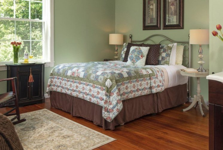 Wood floors in a guest room with light green walls and large bed covered in a coordinating quilt.