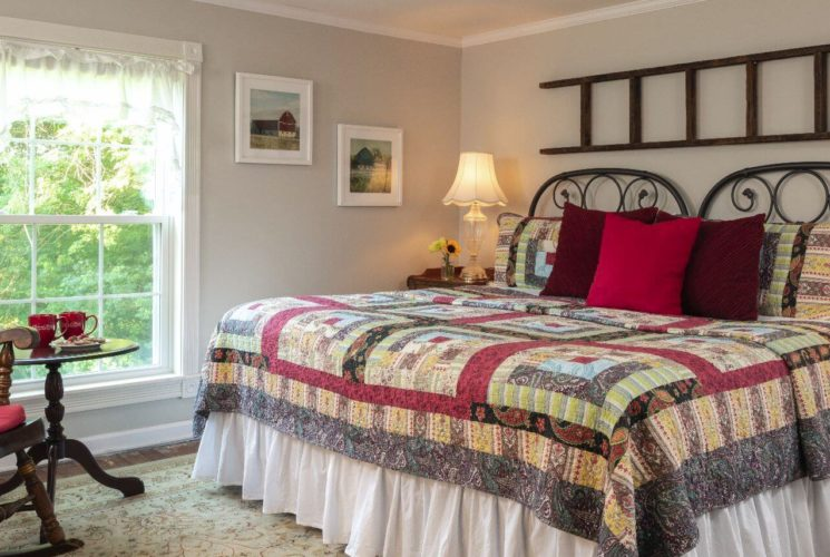 Airy farmhouse room with large windows shown made up with King sized bed..