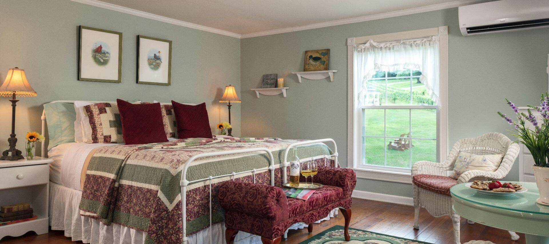 Large room shown with white iron bedstead king bed made up with colorful quilts.