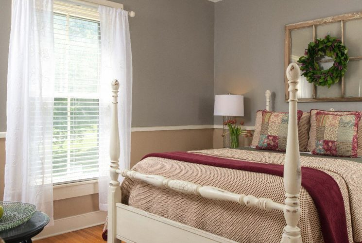 Bright and airy guest room with wainscoting and a white four-post bed.