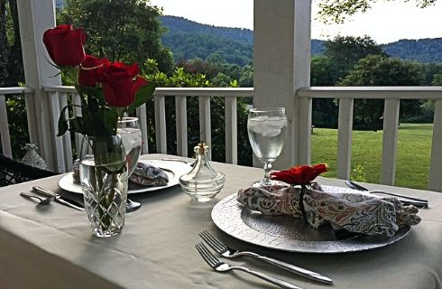 Table set for two on a porch overlooking beautiful mountain scenery.
