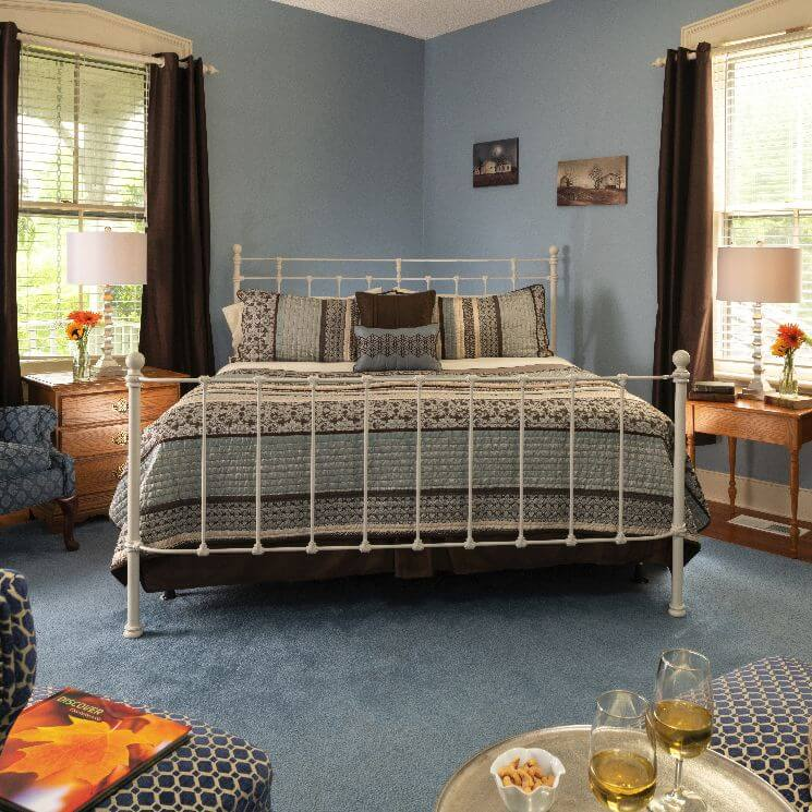 Bright and airy room with blue walls and carpet and a white bedstead.